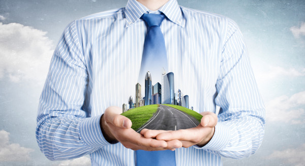 Close-up-of-businessman-holding-city-model-in-hands-600x327